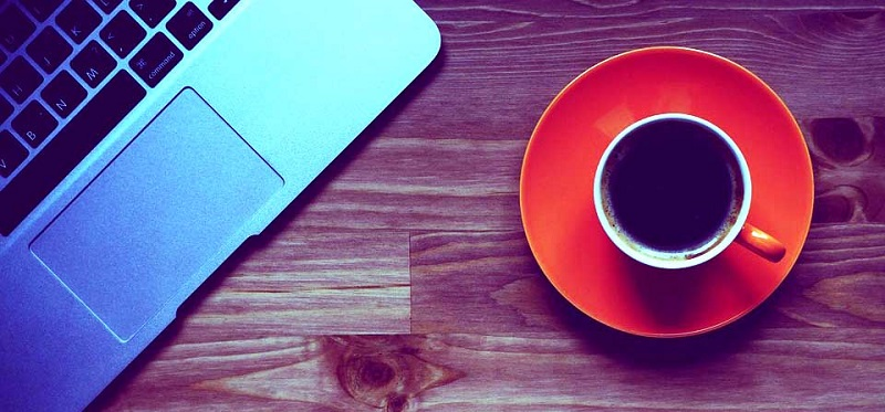 multi-genre author writing laptop coffee